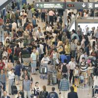 Passengers jam an arrival lobby at Narita International Airport in Chiba Prefecture last month. | KYODO