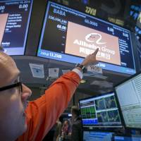 A trader points to the 'BABA' ticker symbol for Alibaba Group Holding Ltd. during its initial public offering at the New York Stock Exchange on Friday. SoftBank Corp. on Saturday predicted a gain of around $4.6 billion through its stake in the Chinese e-commerce behemoth.   REUTERS