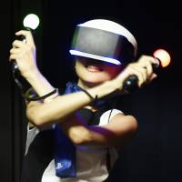 A model wearing Sony's Project Morpheus, a head-mounted display, shakes light sticks to play its PS4 video game console at the annual Tokyo Game Show at Makuhari Messe hall in the city of Chiba on Thursday. | KYODO