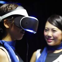 Models show off Sony's Project Morpheus, a head-mounted display designed for use with the PS4 gaming console, at the annual Tokyo Game Show at Makuhari Messe hall in the city of Chiba Thursday. | KYODO