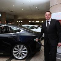 Elon Musk, co-founder and chief executive officer of Tesla Motors Inc., demonstrates how to charge the company's Model S electric sedan following a news conference in Tokyo on Monday.   BLOOMBERG