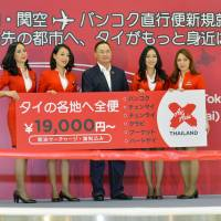 Thai AirAsia X Co. Chief Executive Officer Nadda Buranasiri poses with cabin attendants Monday morning during a ceremony Narita International Airport marking the launch of a new flights servicing Bangkok. | KYODO