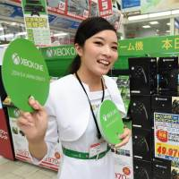 A Microsoft campaign model promotes the Xbox One gaming console at Bic Camera's Ikebukuro outlet in Tokyo on Thursday as the product hit the Japanese market. | AFP-JIJI