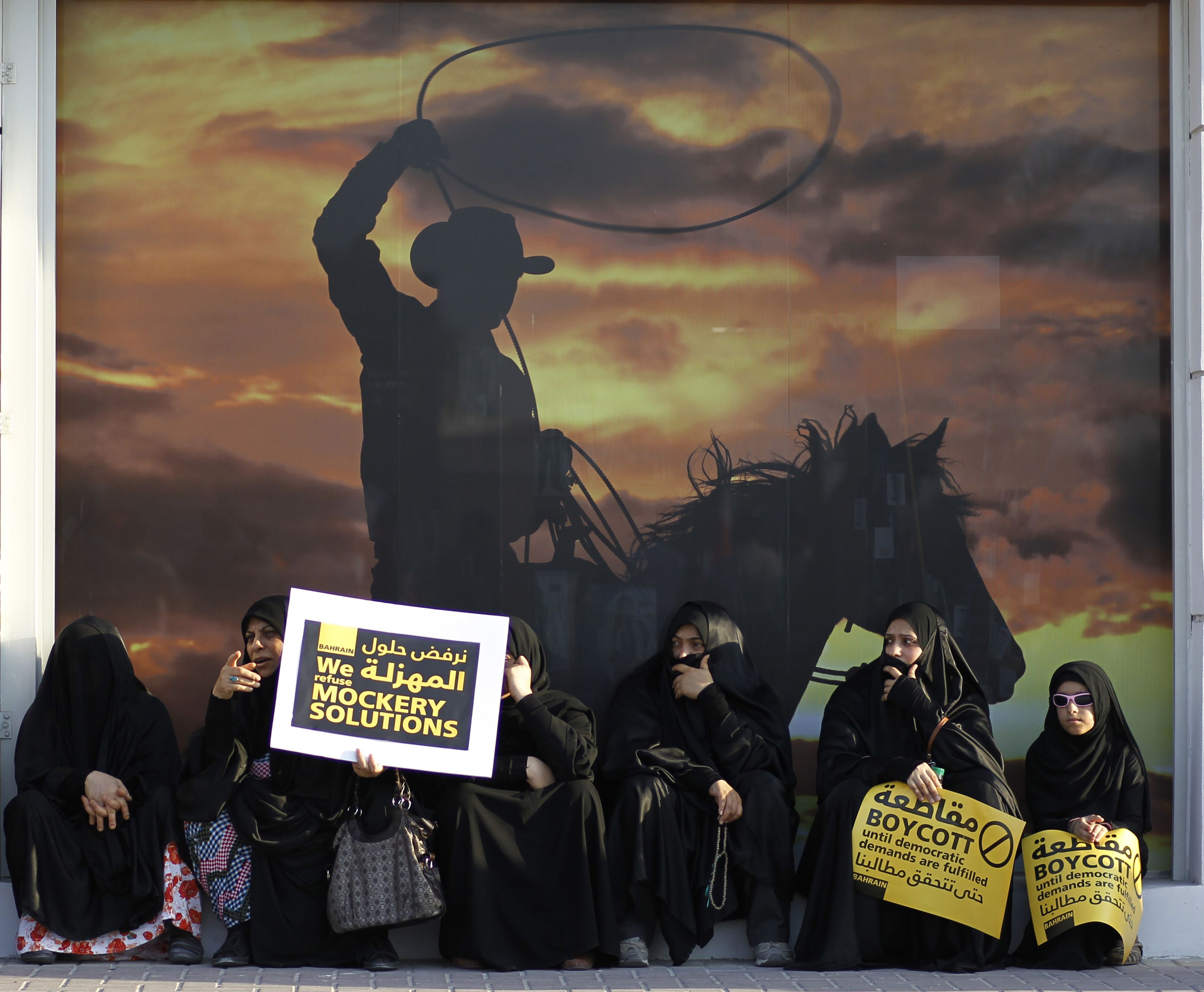 Protesters hold signs as they sit under an advertisement prior to a rally organized by Bahrain's opposition Wefaq organization in Budaiya, west of Manama, on Friday.   REUTERS