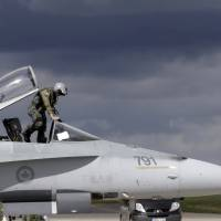A Canadian Air Task Force pilot leaves his CF-188 jet after landing at Siauliai Air Base in Lithuania on Aug. 26. The Royal Canadian Air Force handed over their air policing mission over the Baltics to NATO on Monday. | REUTERS