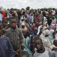 Civilians who fled their homes following an attack by Islamist militants in Bama, Nigeria, take refuge at a school in Maiduguri on Tuesday. Fleeing residents say Boko Haram fighters are patrolling 50 km (32 miles) of the main road between two of several towns the Islamic extremists have seized in a 200-mile (320-km) arc running alongside northeast Nigeria's border with Cameroon. | AP