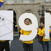 Catalonian separatists hold placards representing the Nov. 9 independence referendum in front of Generalitat Palace before Catalonia President Artur Mas signed a decree Saturday calling for the vote, in Barcelona. | REUTERS