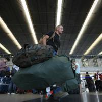 A passenger carries his bags though a terminal at O'Hare International Airport in Chicago on Friday. A fire at an air traffic control center outside the city led to the cancelation of all flights into and out of the airport, one of the world's busiest. | REUTERS