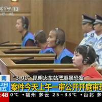Defendants sit in front of police officers at a courtroom in the city of Kunming during the trial of four people accused of participating in an attack at a train station in southwestern China on Friday. | REUTERS