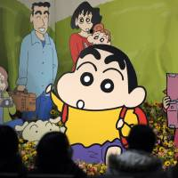 Fans of the Japanese anime character Crayon Shin-chan visit a memorial to the character's late creator, Yoshito Usui, in Tokyo in November 2009. The Indonesian broadcaster that airs the popular cartoon has been warned by a government-sanctioned body to censor content in the show that is inappropriate for children, according to a statement released Monday. | AFP-JIJI