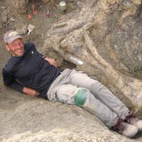American paleontologist Kenneth J. Lacovara poses in 2007 by a tibia bone of a Dreadnoughtus dinosaur at an excavation site in Southern Patagonia in Argentina. The supermassive dinosaur, which would have weighed as much as 60 small cars, is believed to have  perished in a bog some 77 million years ago, palaeontologists said September 4, 2014. Lacovara, an associate professor in Drexel University's College of Arts and Sciences, discovered the Dreadnoughtus fossil skeleton in southern Patagonia in Argentina and led the excavation and analysis. The fossil was unearthed over four field seasons from 2005 through 2009 by Lacovara and his team. | AFP-JIJI
