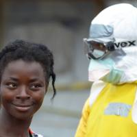 A health worker wears a protective suit next to an Ebola-infected person on Sunday inside the high-risk area of Elwa hospital in Monrovia, which is run by the nongovernmental French organization Doctors Without Borders. | AFP-JIJI