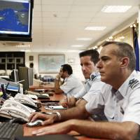 Greek coast guard officers work at the Maritime Rescue Coordination Center at the Shipping Ministry in Piraeus, near Athens, on Thursday. Greece is slipping into a 'danger zone' without the funds or resources to handle a fast-growing wave of refugees trying to enter the European Union from war-torn countries like Syria and Iraq, the government warned. | REUTERS