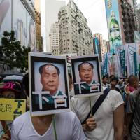 Protesters hold banners depicting a caricature of Leung Chun-ying, Hong Kong's chief executive, during a rally in the city on July 1. The rally was an annual event marking the anniversary of Hong Kong's return to Chinese rule in 1997. | BLOOMBERG