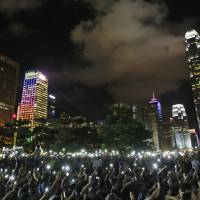 Protesters wave mobile phones during a rally in Hong Kong after China's legislature ruled out open nominations in elections for Hong Kong's leader on Sunday. | AP