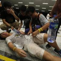 A protester receives help after being pepper sprayed during a confrontation with the police following a rally by the 'Occupy Central' civil disobedience movement in Hong Kong on Saturday. | REUTERS