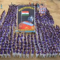 Indian schoolchildren stand in formation at a school in Chennai on Wednesday to celebrate the success of India's Mars Orbiter Mission. Prime Minister Narendra Modi announced the same day that the craft successfully entered orbit around Mars on its first attempt.   AFP-JIJI