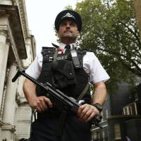 A police officer is seen on duty in Downing Street, central London, on Monday. British Prime Minister David Cameron said the same day he would bring in new laws to give police the power to seize the passports of suspected Iraq- and Syria-bound Islamist fighters. | REUTERS
