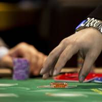 A croupier reaches to collect casino chips at the Global Gaming Expo inside the Venetian Macao resort and casino, operated by Sands China Ltd., a unit of Las Vegas Sands Corp., in Macau on May 20. | BLOOMBERG