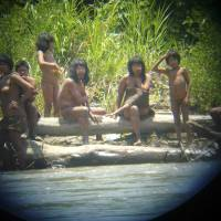 Members of the Mashco Piro tribe observe a group of travelers from across the Alto Madre de Dios River in October 2011 in the Manu National Park, in the Amazon basin of southeastern Peru.   REUTERS