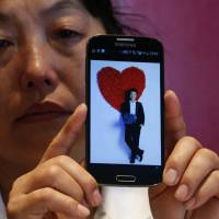 Feng Xuehong, whose son Wang Houbin was on Malaysia Airlines Flight MH370, cries as she shows a picture of him on her mobile phone during an interview in Beijing on July 18. | REUTERS