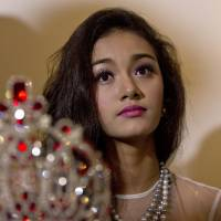 May Myat Noe, Myanmar's first international beauty queen, winner of the 2014 Miss Asia Pacific World, sits with her crown that she allegedly ran away with, during a news conference in Yangon on Tuesday. | AP