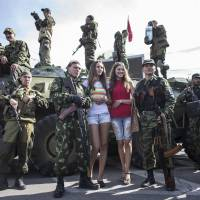 Women pose with pro-Russian rebels during a parade in Luhanks, eastern Ukraine, on Sunday. Ukraine's defenae minister said the same day that NATO countries were delivering weapons to his country to equip it to fight pro-Russian separatists and 'stop' Russian President Vladimir Putin.   REUTERS