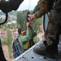 An Indian tourist being evacuated is lifted into a helicopter in Srinagar, India, on Tuesday. | AP