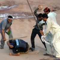 Supporters of Pakistani politician Imran Khan beat a policeman during an anti-government protest in Islamabad on Monday. Deadly clashes since the weekend have raised the specter of military intervention in protests that have rocked the nation's capital. | AFP-JIJI