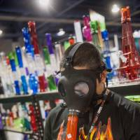 A man displays a gas mask modified with a water pipe that can be used to smoke marijuana during the Champs Trade Show in Las Vegas last December. | BLOOMBERG