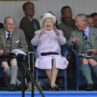 Prince Philip, Queen Elizabeth II and Prince Charles cheer as competitors participate in a sack race at the Braemar Gathering in Braemar, Scotland, on Sept. 1, 2012. | REUTERS