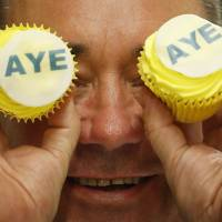 SNP leader Alex Salmond visits Brownings bakery in Kilmarnock, Scotland, on Wednesday, where he was presented with 'Aye' branded cakes in support of the independence campaign. The British pound slipped sharply after an opinion poll on Tuesday revealed a jump in the number of people advocating severance of the country's 307-year union with the U.K. | AP