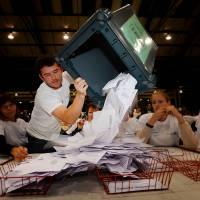 A worker tips out a ballot box in the Aberdeen Exhibition and Conference Centre in Aberdeen, Thursday, immediately after the polls closed in the referendum on Scotland's independence.
