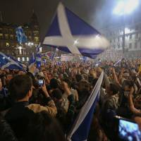 Pro-independence 'yes' campaign supporters wave the national flag of Scotland as they demonstrate Thursday in George square in Glasgow. | BLOOMBERG