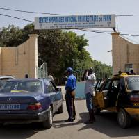A security guard working at Dakar's University Hospital Fann speaks to people inside a car Friday. The hospital is treating a  man with symptoms of the Ebola virus. The effort to contain Ebola in Senegal is 'a top priority emergency,' the World Health Organization said Sunday. | AP