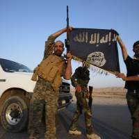 Iraqi Shiite militia fighters hold the Islamic State flag as they celebrate after breaking the Islamic State militants' siege of Amerli on Sept. 1.   REUTERS