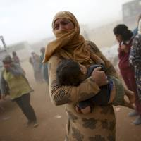 A Syrian Kurdish refugee awaits transport during a sandstorm on the border near the Turkish town of Suruc on Wednesday. In the turmoil of Syria's civil war, Khorasan recruiters are seeking European and American Muslims to deliver attacks on their home turf.   REUTERS