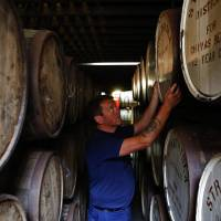 An employee checks a cask of Chivas Regal blended Scotch whisky at Pernod Ricard SA's Strathisla distillery in Keith, Scotland, on Aug. 5. | BLOOMBERG