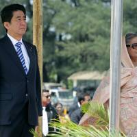 Prime Minister Shinzo Abe reviews a guard of honor with Bangladeshi Prime Minister Sheikh Hasina after arriving at the airport in Dhaka on Saturday. | AP