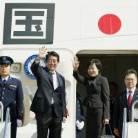 Prime Minister Shinzo Abe and his wife Akie wave before boarding a jet Monday at Haneda airport in Tokyo on the way to the U.N. General Assembly in New York. | KYODO