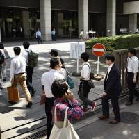 People line up in front of the Tokyo District Court on Friday morning for numbered lottery tickets to attend the trial of pop singer Aska, who was handed a suspended sentence later in the day over his drug use.   KYODO