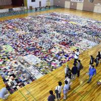 A patchwork blanket made from donated knitted squares appears to have set a new world record. The blanket is the work of a German resident of Yokohama and around 80 people living in disaster-hit Ishinomaki, Miyagi Prefecture. | KYODO