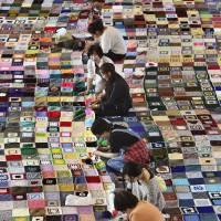 Volunteers work on stitching together a 476-sq.-meter blanket Saturday in Ishinomaki, Miyagi Prefecture. | KYODO