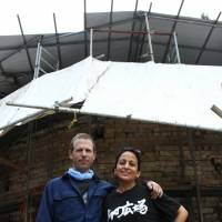 Married sculptors Steven Ward and Ximena Elgueda have spent the past 14 years building a terra-cotta amphitheater for the performing arts. They are seen in front of a kiln erected to bake the stage's ceramic rear wall, which directs sound at the audience.   CHUNICHI SHIMBUN