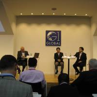 Upper House member Yoshimasa Hayashi (on stage, right), Heizo Takenaka, director of the Global Security Research Institute (center), and moderator Nik Gowing, an international broadcaster and journalist, discuss the consumption tax hike and other economic issues in Japan at the G1 Global Conference 2014 in Tokyo on Monday. | MINORU MATSUTANI