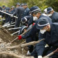 Police search for the remains of people still missing since the March 11, 2011, disasters in Namie, Fukushima Prefecture, on Thursday. | KYODO