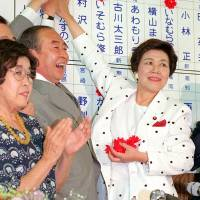 Takako Doi (right), then head of the Social Democratic Party, puts a red fake flower on the name of a successful SDP candidate after the 1989 Upper House election at the party's headquarters in Tokyo. | KYODO