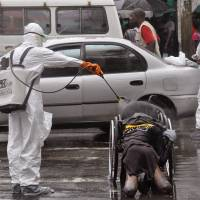 Health workers disinfect the body of an amputee suspected of having the Ebola virus on a busy street in Monrovia on Tuesday. | AP