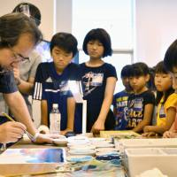 Elementary school students in the city of Shizuoka receive a drawing lesson from animator Nizo Yamamoto, known for his art direction on a number of Studio Ghibli films, on July 12. | KYODO