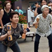 People work out with wooden dumbbells outside a temple in Tokyo on Monday to celebrate Respect for the Elderly Day. | AFP-JIJI